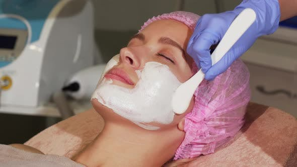 Thumbnail for Happy Woman Smiling During Facial Mask Application at Beauty Salon