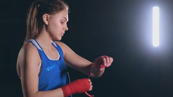 Thumbnail for Medium Shot A Beautiful Female Boxer Pulls Red Bandages Onto the Wrist of a Female Fighter