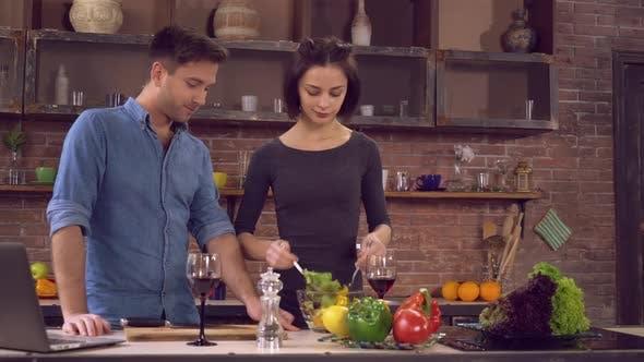 Frau rührt die Salat Mann stehen in der Nähe