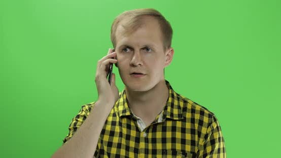 Cover Image for Caucasian Young Man in Yellow Shirt mit Handy für Anruf