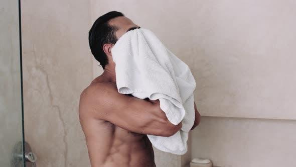 Man wiping himself with towel in bathroom