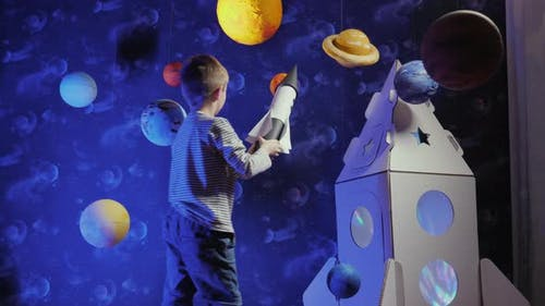 Little Boy Playing with Toy Rocket Flying Around the Planets
