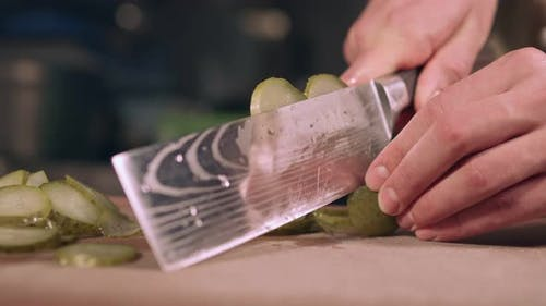 The chef professionally slices a cucumber