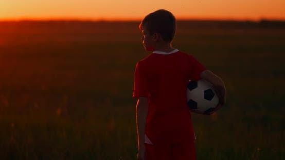 Thumbnail for The Camera Follows the Boy Walking at Sunset in the Field with the Ball
