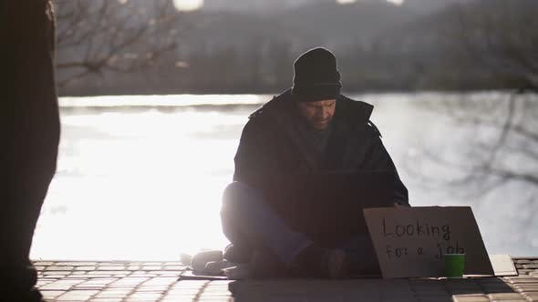 Homeless Bearded Male Begging and Using Laptop