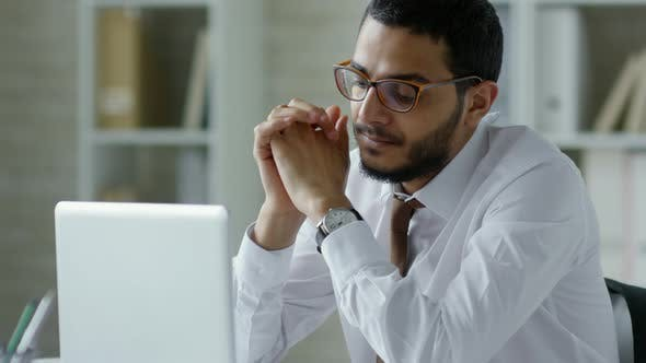 Thumbnail for Middle Eastern Businessman Reading Report on Laptop