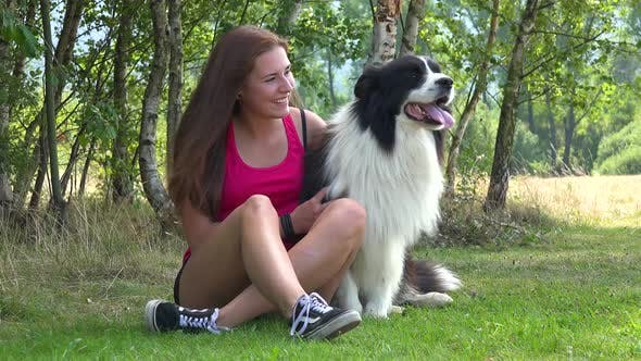 Thumbnail for A Young Beautiful Woman Sits on Grass in a Meadow with a Border Collie and Smiles at the Camera