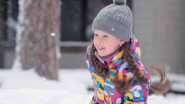 Thumbnail for Pretty Little Girl in Color Jumper Plays with Snow in Park
