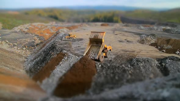 Tilt Shift Panorama Yellow Dump Truck Unloads Rocks and Gravel