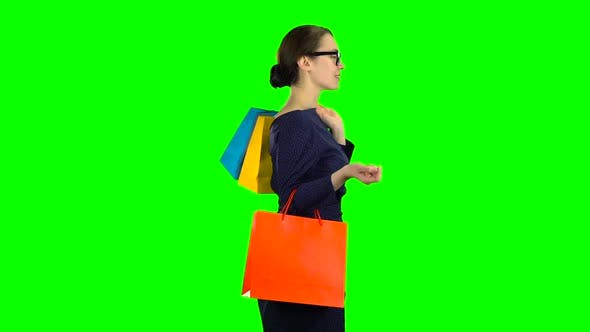 Thumbnail for Girl with Packages in Her Hands Is Walking Along the Street. Green Screen. Side View