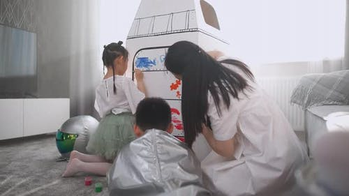 Handheld an Asian Female with Kids Play in the Living Room at Home a Boy in an Astronaut Costume