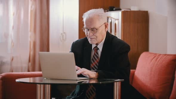 Thumbnail for Elderly Grandfather - Old Grandfather with Glasses Is Typing on a Computer