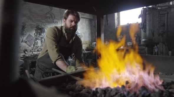 Thumbnail for Blacksmith Looking at Burning Coals