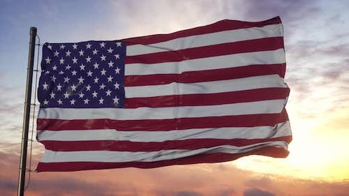 Flag of America Waving in the Wind Against Deep Beautiful Sky at Sunset