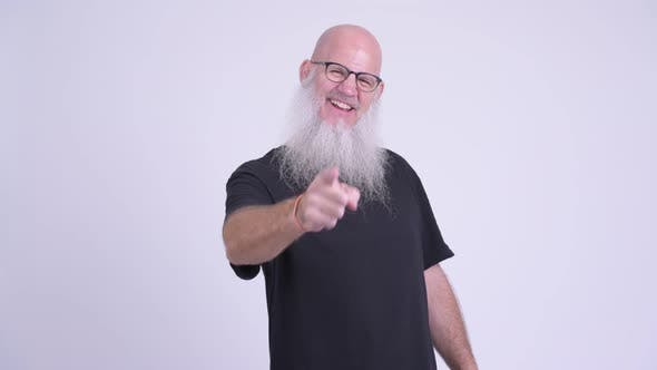 Cover Image for Happy Mature Bald Bearded Man Smiling While Pointing To Camera