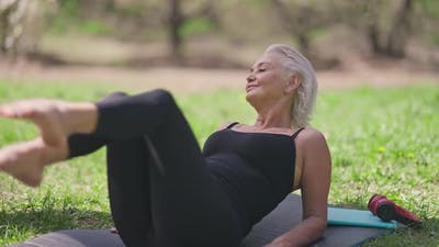Satisfied Fit Senior Woman Lying on Exercise Mat Smiling Doing Bicycle Exercise