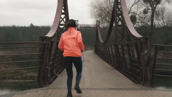 Thumbnail for Woman in headphones is running across bridge in park.