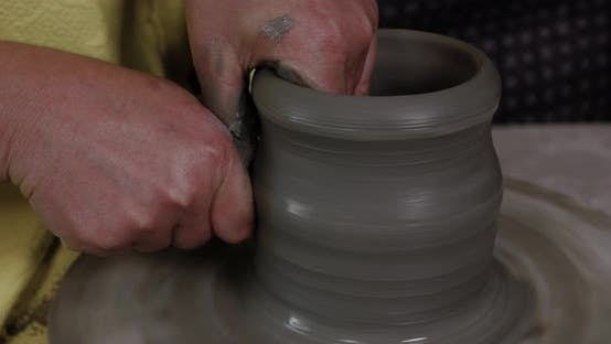 Hands work the pottery on the lathe.