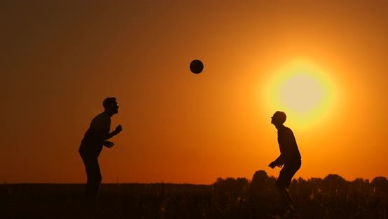 Thumbnail for Two Boys Playing Soccer at Sunset. Silhouette of Children Playing with a Ball at Sunset