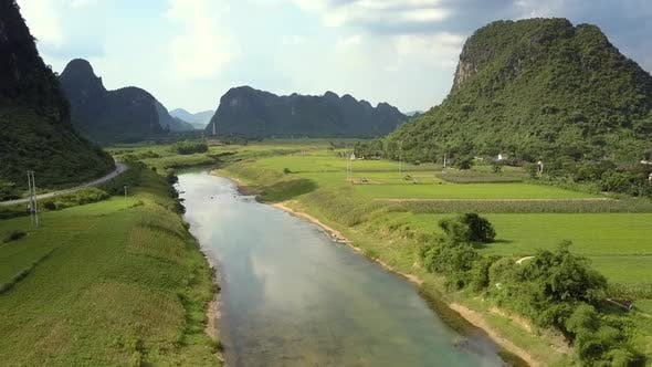 Thumbnail for Aerial Motion Above River Crossing Fields Among Mountains