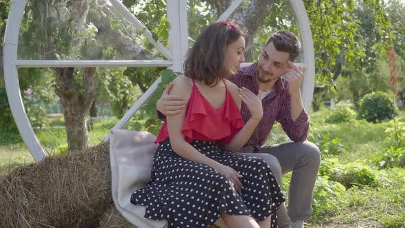 Young Woman and Man Sitting in the Garden the Guy Hugging His Girlfriend