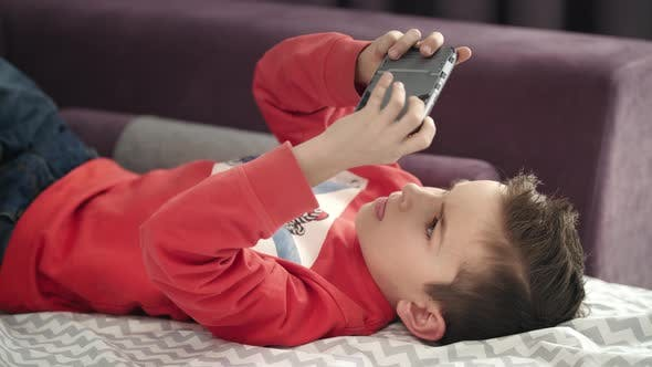 Thumbnail for Boy Playing Mobile Game on Smartphone on Sofa. Kid Playing Mobile Phone