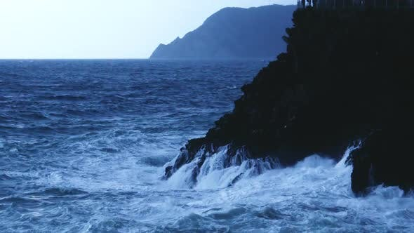 Thumbnail for Blue sea water waves crashing into rocky cliff forming foam, stormy weather