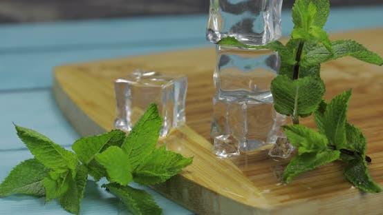 Eiswürfel und Minzblätter isoliert auf Holzschneidebrett