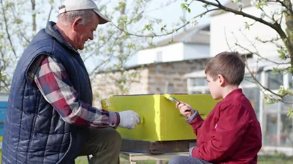 Beekeeper Family an Old Man and a Male Child Work in an Apiary, Prepare Beehives for the Summer