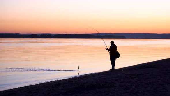 A Man Caught a Fish. A Silhouette of a Man Fishing at Sunrise By the River. The Yellow Sun Rises