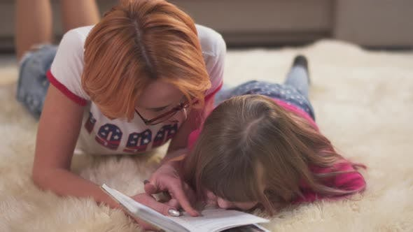 Thumbnail for Portrait Beautiful Mother and Cute Little Daughter Are Lying on the Carpet on the Floor