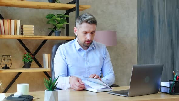 Focused man at home office in wireless earphones writes information notebook looks laptop computer