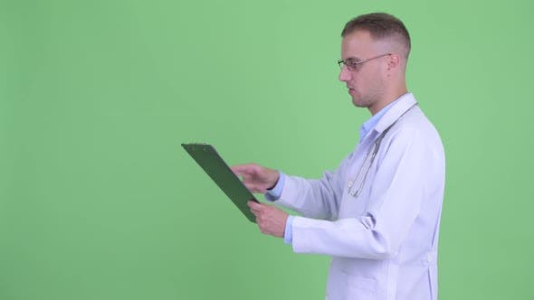 Thumbnail for Profile View of Happy Handsome Man Doctor Talking While Holding Clipboard