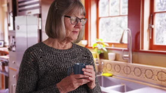 Thumbnail for Aged woman holding drink with thoughtful look sneezing in kitchen setting