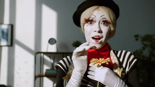 Slow Motion Portrait of Attractive Female Mime Holding Flower and Smiling Looking at Camera Indoors