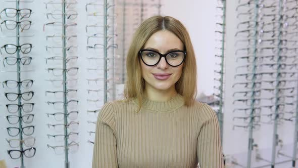 Attractive Young Blonde Woman Standing in Front of the Camera Dressed in Transparent Glasses with a