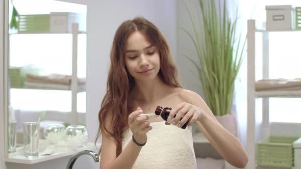 Jeune femme dans serviette de bain boire sirop pour la guérison de la toux dans la salle de bain
