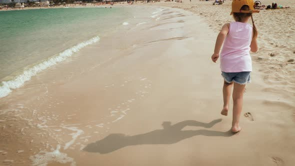 Cover Image for A Cute Girl Running Along the Beach