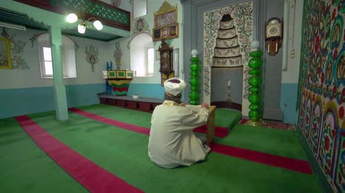 Muslim Mosque Teacher is reading the Quran in Small Historic Wooden Masjid