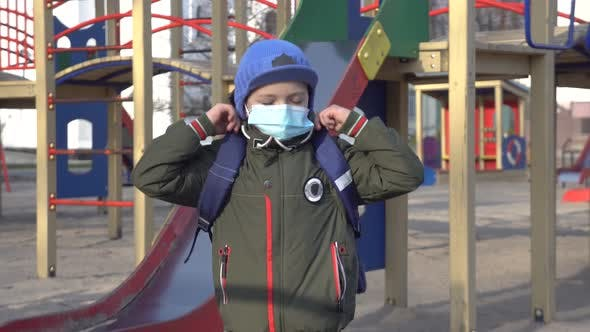 Thumbnail for Caucasian Schoolboy in Face Mask Standing Alone on Children's Playground