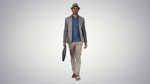 Casual arabian man walking in a hat and with a briefcase