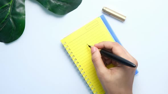Close Up of Women Hand Writing on Notepad.