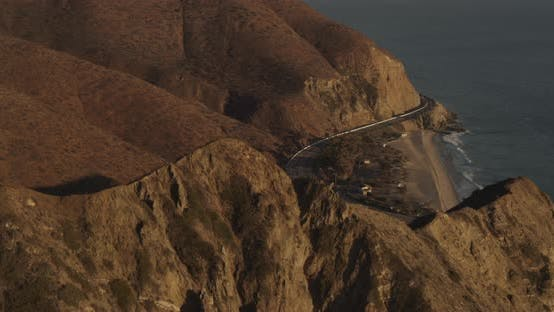 Thumbnail for Aerial helicopter shot, tracking airliner as it banks right above mansions and past mountains in haz