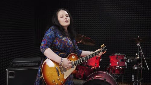 Female pop country jazz music artist is playing guitar, performing song