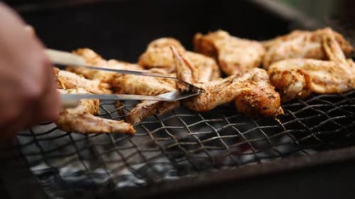 Man Using Metal Tongs To Turning Chicken Wings Which Are Being Grilled on Barbecue