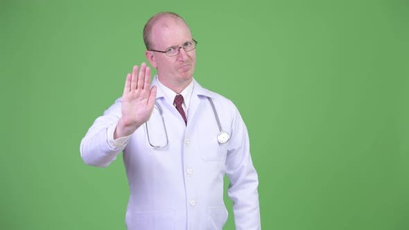 Cover Image for Mature Bald Man Doctor with Stop Hand Gesture