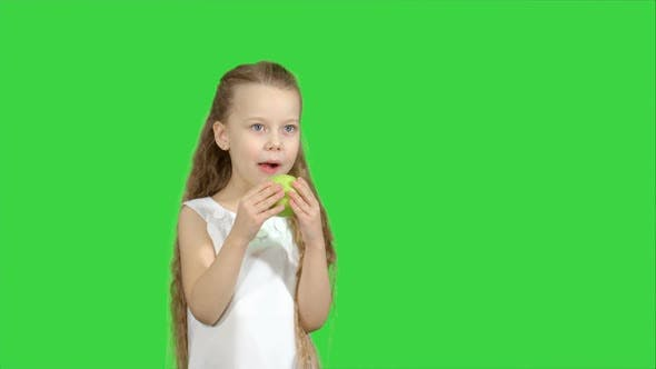 Thumbnail for Portrait of a Little Girl Eating Green Apple on a Green Screen, Chroma Key