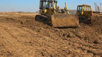 Two Bulldozers Are Working