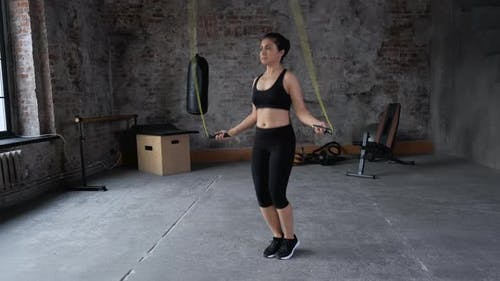 Young Indian Athlete woman skipping with skipping rope in gym