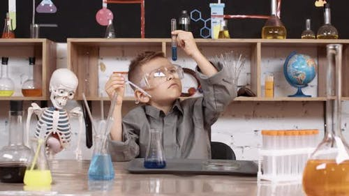 Laboratory Experience in a Chemistry Lesson, the Boy in Protective Glasses Pours a Blue Liquid Into